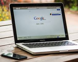 laptop with Google search page open next to phone on wooden table