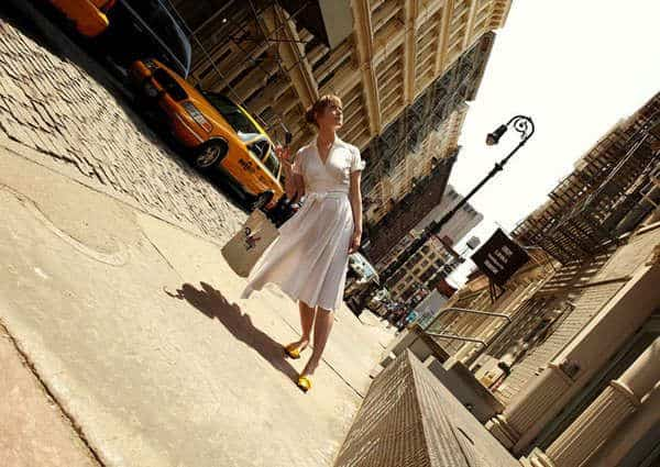 woman in white dress leaning at an angle or tilt in the street